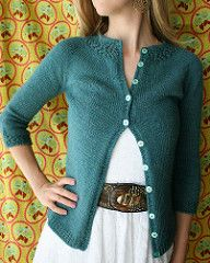 """Named for the Latin word for """"jewel"""" Gemma is a simple cardigan with lace """"necklace"""" at the collar that is knit in one piece from the top down with a circular yoke. Short rows are used to raise the back collar, and sleeves are knit down from the yoke. The slightly puffed, three-quarter length sleeves have cuffs of the same lace as the collar. Gemma is a flattering cardigan that is sure to become a wardrobe staple!"""