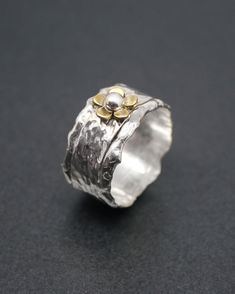 Handmade wide silver ring with brass flower and silver detail. The brass daisy measures 8mm and has a silver bead centre. The hammered band is 10mm wide.