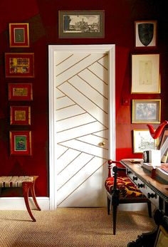 White door with brass nailhead trim against a red wall.