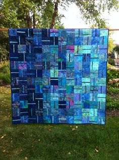 """For my friend"". Contemporary pattern using shades of blue batiks. Quilting pattern echoes single stripe."