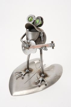 Musical Frog on Lily Pad Statue - Funny frog sculpture features a little frog riding on a lily pad playing his guitar. Uniquely crafted from metal this sculpture may vary slightly due to the handmade process