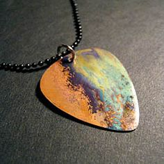 This guitar pick necklace was created from copper that was heated to have bright, iridescent swirls of color.