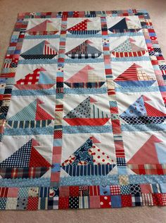 """sailboat quilt.  Quilt finishes 50"""" x 80"""".  Sails made from various sized HST and waves made by rick rack."""
