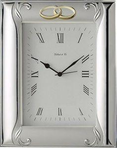 Elegancki zegar w srebrnej ramce zdobionej dwoma splecionymi obrączkami, stanowi doskonały prezent z okazji 50 rocznicy ślubu dla rodziców. #rocznica #slub