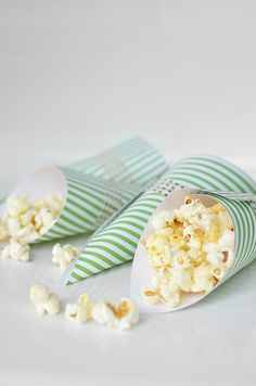 Wrap scrapbook paper into a cone, adhere with washi tape, and fill with popcorn.