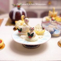 Three delightful festive Patisserie Cakes    A Fondant Swan andt snowman on whipped cream decorated with a sprig of festive holly and a cream