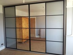 Sliding doors with a black frame and oriental bars. Two doors with pure white glass; two with mirrors.
