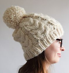 Free knitting pattern for Cable Pom Pom Hat - The chunky cables ... 0c53dba9f372