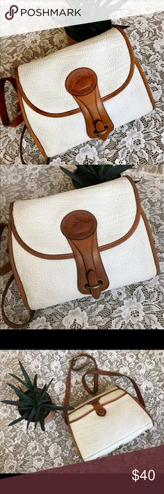 """Vintage Dooney & Bourke 🦆 Vintage Dooney & Bourke Medium Essex Shoulder bag in white with British Tan piping. Pebbled All-Weather Leather.  1 slipper pocket on back with brass pommel and tan closure. Removable/adjustable shoulder strap. 10"""" x 8"""" 4.5"""" drop length-23"""" at longest and 21"""" at shortest.  This purse is in fair condition-could use a little love from an expert! The lining has pen marks as well. Sadly it is missing the brass duck fob. Gorgeous classic style. Retailed at $235 in 1996…"""