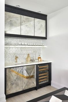 Chic contemporary black and white wet bar is fitted with antiqued mirrored cabinets positioned beside a glass front mini wine cooler and beneath a white marble countertop finished with a small sink with a brushed gold faucet. Küchen Design, House Design, Interior Design, Design Ideas, Home Bar Designs, Wet Bar Designs, Muebles Living, Built In Bar, Small Sink
