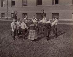 "12 boys and two instructors on the lawn of the Kindergarten Department of the Perkins Institution for the Blind in Jamaica Plain, Massachusetts. The photograph is titled ""Kindergarten Games. The Wheelwright."" The boys are arranged in a circle with one boy at the center circa 1893. Visit the Perkins Archives Flicker page: http://www.flickr.com/photos/perkinsarchive/collections/"