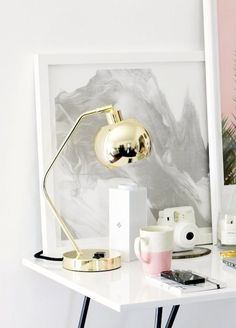 Bright work space with a gold desk lamp, pink ceramic mug, marble notebook and phone case, wireless speaker, framed art & instant camera #homedecor #interiordesign #office
