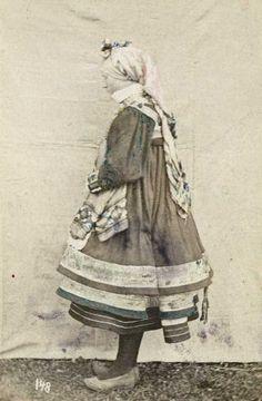 Digitalt Museum - 148. Brudedrakt sett fra siden, Setesdal, Aust-Agder. Fotografert stående utendør mot opphengt bakteppe. Visittkortformat.
