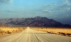 Una strada di terra battuta si perde tra le quinte montuose dell'interno.