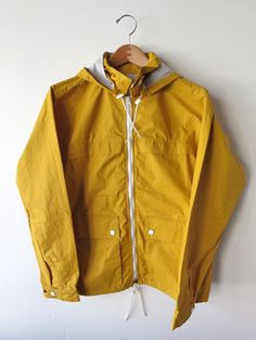 MHL Spring Anorak Margaret Howell's collections don't often feature a lot of bright colours, but the summer rain jacket is a classic reference to bring out a nice pop of yellow. The simple zip-up anorak is a great casual jacket for the current climate.