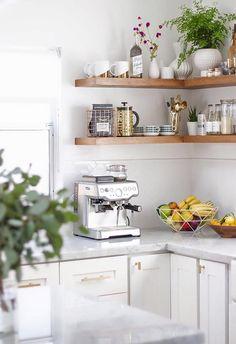 Cozinha com prateleiras abertas, plantas e flores, objetos bonitos e arrumados