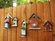 Birdhouse facades on fence - Cute!