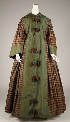 Silk wrapper. Met Museum dates as 1850s, but those box pleats are more '60s and the flat bows marching down the front were a popular decoration in the second half of the '60s. I think we're looking at an early '60s dress remade into a wrapper, 1865 or later. Bell sleeves remained a feature of wrappers even after the narrow coat sleeve took over daywear.