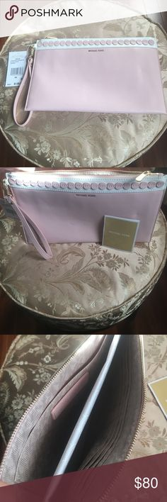 Michael Kors extra large clutch This large clutch is light pink and white with gold lettering, gold zipper and gold clasp. The wrist band is removable. Brand new, never used. Willing to take reasonable offers Michael Kors Bags Clutches & Wristlets