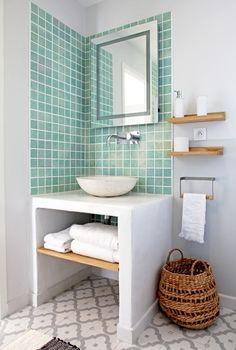 Carreaux méli-mélo à la salle de bains... Une maison à la déco métissée qui nous fait voyager  En associant de petits carreaux vert d'eau à un sol à motifs orientaux, en optant pour une vasque en pierre blanche, puis en ajoutant quelques accessoires en bois naturel et un panier en rotin, Leslie et Jean-Marie ont réussi à composer, dans la petite salle de bains, une décoration métissée et personnelle à partir de peu d'éléments. ©  Elodie Rothan