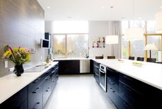 Play with contrasts of black cabinets against white walls and countertops. Doing away with upper cabinets entirely will certainly help with brightness, both in terms of natural light and visual space