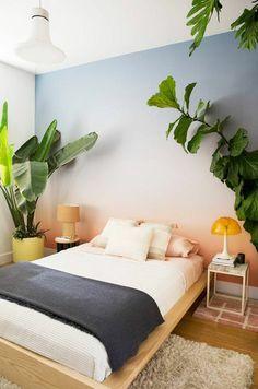 peinture chambre adulte avec mur en bleu au dessus du lit et les autres murs blancs avec des grandes plantes vertes des deux cotes du lit