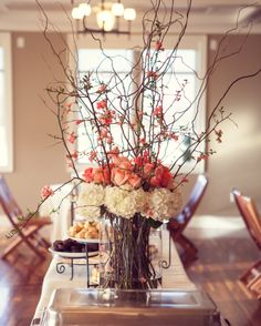 Spring centerpiece. Flowering quince branches. White hydrangeas. Coral and peach roses.