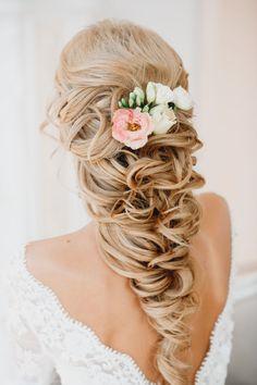 Peinados para el día de tu boda, chica usando un peinado suelto con chinos y accesorios de rosas