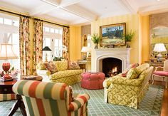Living Room in Yellow, Green, and Red  With walls sporting a strong yellow-and-white-striped Cowtan and Tout wallpaper, this living room is grounded by the green rug with a trellis motif. Spirited fabrics show up in pairs--on facing sofas in front of the fireplace, in stripes on armchairs flanking a round occasional table, and on floral drapery panels that dress sets of French doors. The coral ottoman in the center of the room is a solid star. (Traditional Home)