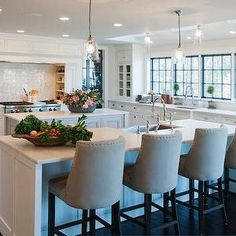 Crown Point Cabinetry - kitchens - shaker cabinets, white shaker cabinets, nickel cabinet pulls, honed white marble, honed white marble countertop, two kitchen islands, dual kitchen islands, island overhang, stainless steel apron sink, bridge faucet, bridge gooseneck faucet, gray kitchen island, espresso wood floors, stainless steel wall oven, double wall oven, warming drawer, stainless steel warming drawer, pull out spice cabinet, pull out spice rack, stacked marble tile backsplash, range alcove, gas range, gas stove with griddle, cabinet front range hood, hidden vent hood, concealed exhaust hood, steel paned windows, steel kitchen windows, undermount stainless steel sink, countertop kitchen hutch, countertop hutch, built in kitchen hutch, skylights, mini glass pendant, semi flushmount glass pendant, linen barrelback counter stools, 1940s french counter stool, french style counter stool, 2 kitchen islands, double islands, double kitchen islands, stainless steel apron sink, gray center island, kitchen island with shelf, island with shelf, cooktop alcove, stove alcove, cooktop spice racks, glass door hutch, built in hutch, gourmet kitchens,