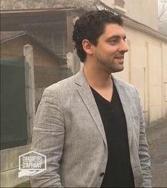 Romaric porte un veston gris avec un pull noir.