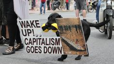 """The """"anti-capitalism"""" dog joins a protest against austerity measures in central Athens in 2011. Alexander Besant"""