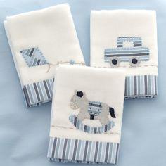 As Fraldinhas de boca são bordadas à mão com desenhos dos Brinquedos e detalhes em azul. Feitas em algodão, têm barra de tecido estampado com listras azuis, tema da coleção. São 03 unidades de 32 x 32 cm cada.