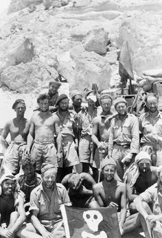 A posed group portrait of personnel from 'Y' Patrol returning to Kufra after a successful raiding sortie. Back row (left to right): Trooper 'Tankie' Babb ( Tank Corps); Corporal Jack Harris (Somerset Yeomanry); Gunner James D Patch (RA); Sergeant Derek (Hutch) Hutchins (Somerset Yeomanry); Lance Corporal Arthur (Tich) Cave MM (Somerset Yeomanry); Lance Corporal Brian Springford (Somerset Yeomanry); Trooper Kenneth Tinckler (Cheshire Regiment); Craftsman Alf Tighe MM (REME); Trooper 'Jesus'…