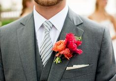 Charcoal gray suit with a bright pink and orange boutonniere. Love the pop of color.