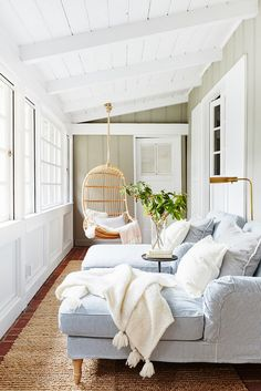 sun room, wicker swing basket chair, pale blue chaise longue chairs, cream throw, jute rug, white panelling