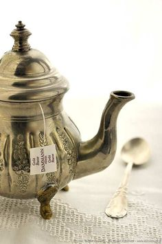 Can't believe they've set up this photo with a teabag tag dangling from an heirloom silver teapot!  Please -- such a pot demands high grade loose tea and a strainer.