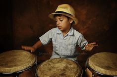 A young conga hand drum player, with a brim hat that says kool in progress.... by Jorge Almaraz...