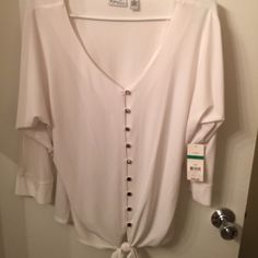 Poly top White with silver buttons this cute top is very versatile ...it sits just below waist Tops Blouses