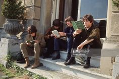 10th May 1965. The Beatles, sitting on a step reading, at Cliveden House in Buckinghamshire during the filming of 'Help'.