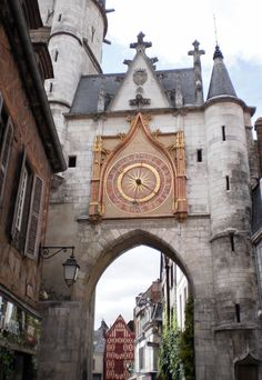 Auxerre, Burgundy, France | The magnificent sundial on the Tour de l'Horloge. (The Clock Tower) It was built in 1483 as part of Auxerre's fortifications. It is now mainly of interest for the two colourful clock faces, with one 'sun' hand that tells the time of day and another 'moon' hand that follows the lunar month, rotating every 29.5 days.