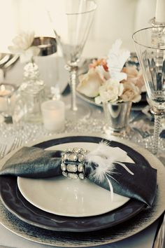 Diamond crystals, sequin table cloth , crystal ,& a wisp of white feathers contrasting with the chic black... I LOVE this a glamorous place setting !!!!