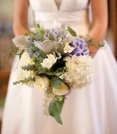 Bouquet of hydrangeas, silver leaf and lamb's ears accented with herbs like mint, sage and thyme.