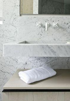 Sleek white marble bathroom vanity and white taps