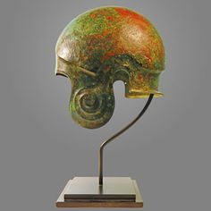 Circa 550-500 BC An ancient Greek bronze helmet of the Chalcidian type, with a carinated ridge around the top, rising to a point over the forehead, and large repoussé volutes on the rounded cheek pieces.