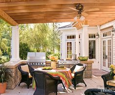 Shaded by a pergola, cooled by a ceiling fan, and furnished to the nines, this kitchen draws people outside and surrounds them with indoor comforts. The far stone wall houses a gas grill and a four-burner cooktop, which amplify cooking options. Smooth stone slabs topping the wall provide food-prep surfaces and landing areas for in-process dishes.