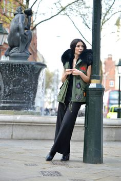 Anisa Sojka styles army green South West Ten vest with chunky hooded fur collar | | Low v-neck Zara top with lace cup sleeves | Black wide-leg loose trousers | High heeled Paper Dolls ankle boots | Dainty silver and gold Lucky Eyes necklaces | Brunette tucked in hair | Fashion blogger street style photographed by David Nyanzi in London
