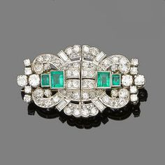 An emerald and diamond double-clip brooch, circa 1935 Each opposing clip of scrolling and geometric design, centrally-set with two rectangular step-cut emeralds within an openwork surround set with old brilliant and baguette-cut diamonds.