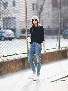 Danielle Bernstein of We Wore What in polka dot denim jeans, a navy crew neck sweater, a beanie, and white sneakers