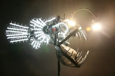 """Deep Sea Angler Fish"" by Justin La Doux is a stunning five foot long sculpture of an anglerfish made out of recycled objects. A light dangling above the fish lures the viewer closer. If the viewer draws near a motion sensor activates additional lights in the eyes and body of the fish. The sculpture is made out of knives, a bicycle, a shovel, and many other scavenged parts."